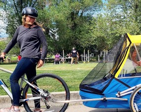 Mom, Karen and 22-year-old Kai try out one of the new adult bike trailers available through the Kelowna Activity & Program Guide this fall.