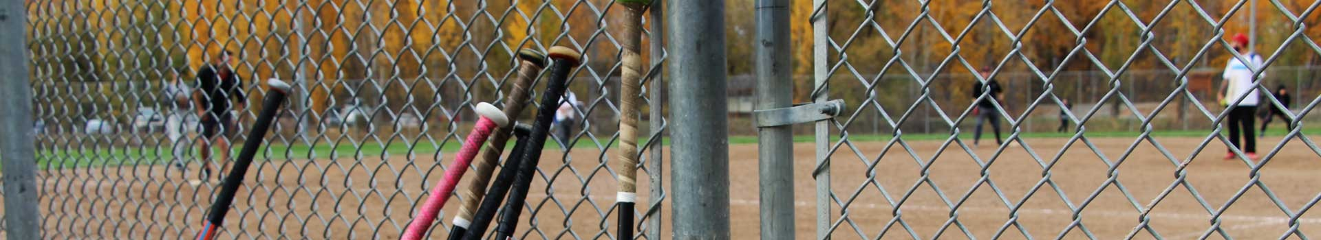 slo pitch players seen through fence